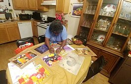 Derotha Payne-Obie mounts a recently completed puzzle at her dining room table. Prior to the pandemic, she attended the Lewis Senior Center. It closed in March under local and state mandates. (Tamara Cunningham)