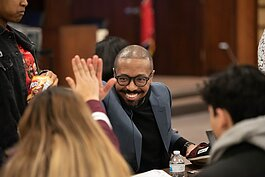 Edward Bogard, founder of Memphis-based nonprofit shoe manufacturer SoGiv, high fives a student at the three-day teen design charrette benefiting Shelby County Schools. (Demarcus Bowser)