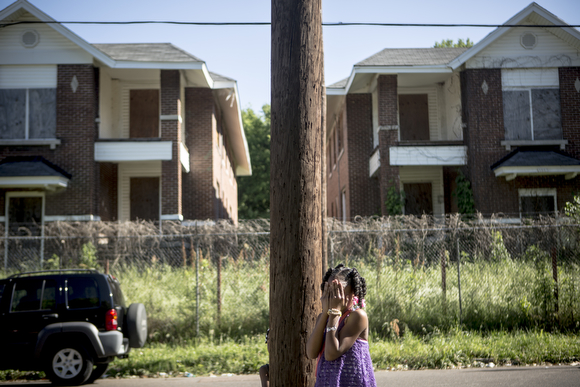 A young girl plays hide and seek in front of shuttered apartment buildings on Tate Street. (Andrea Morales)