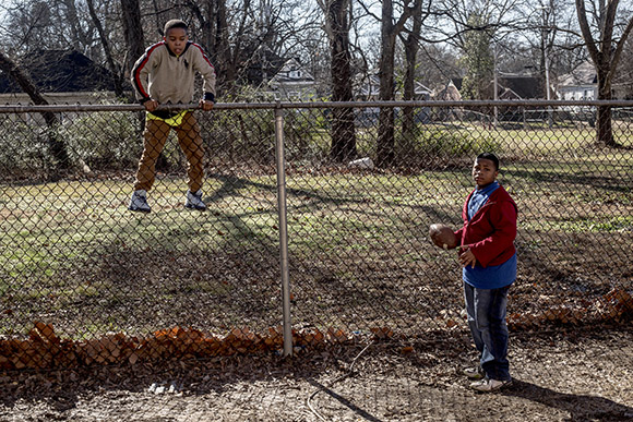 After retrieving a stray football from the next yard, a  student climbs back over the fence during recess at the Memphis Scholars Caldwell- Guthrie School in Smokey City.