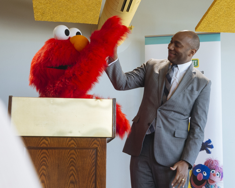 Shelby County Mayor Lee Harris high-fives Elmo at a December 4 press conference to announce a new partnership with Sesame Street in Communities. (Ziggy Mack)