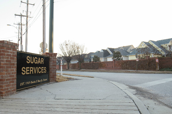 Sugar Services, an active industrial site, faces a dense residential community.