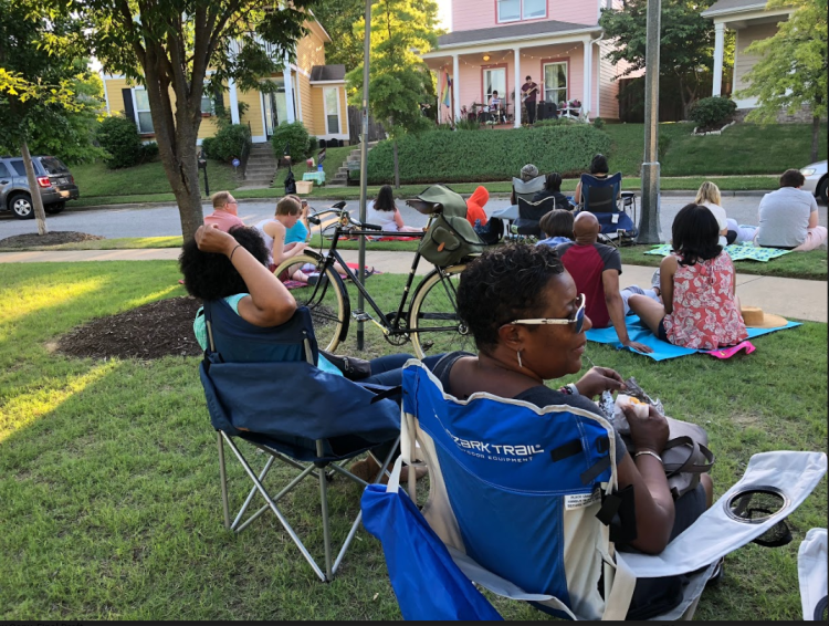 Uptown Community Association member Tanja Mitchell enjoys the concert with her friends. It was Mitchell who first proposed applying for the grant that made the porch series possible. (Cole Bradley)