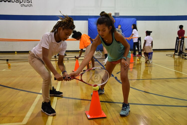 Ella DeJesus. right, helps a friend hone her tennis skills. Peer teaching is very important to Tennis Memphis because it is an effective way to build skills and friendships. (Tennis Memphis)