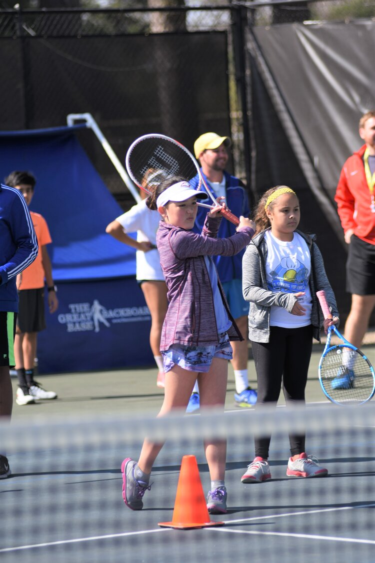 Shelby Callaghan, front left, practices hitting the tennis ball while Dianik Baldoquin waits her turn at Tennis Memphis youth program. (Tennis Memphis)