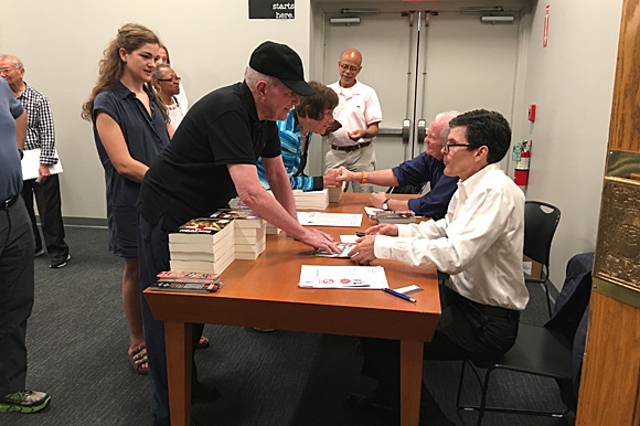 Dr. Jim Bailey (foreground) and Dr. G. Scott Morris sign copies of their books, while Dr. Clarence Davis (center background) answers questions from those who attended the inaugural Healthy City Town Hall meeting, held Sep. 16 at Novel bookstore.