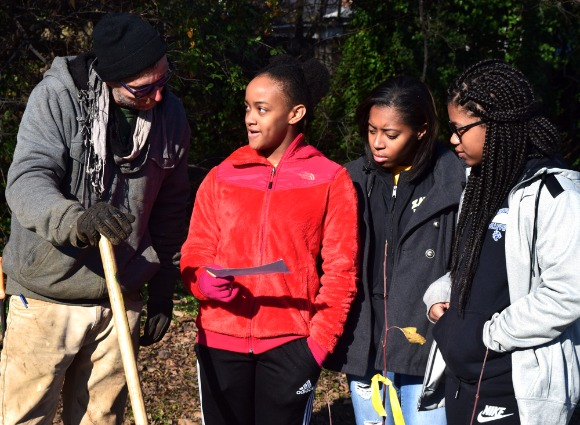 Mike Larrivee works with students from the Bridge Builders program at a December 9 planting event.