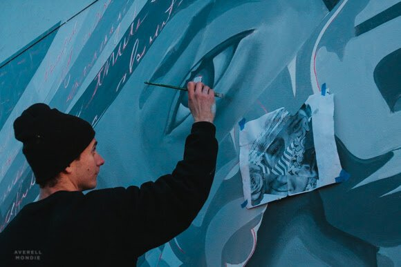 Brandon Marshall paints a temporary mural funded by UrbanArt Commission. (Averell Mondie)
