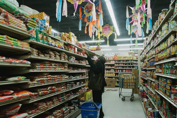 A shop reaches for an item off a top shelf at the Viet Hoa Food Market in Madison Heights. (High Ground News)